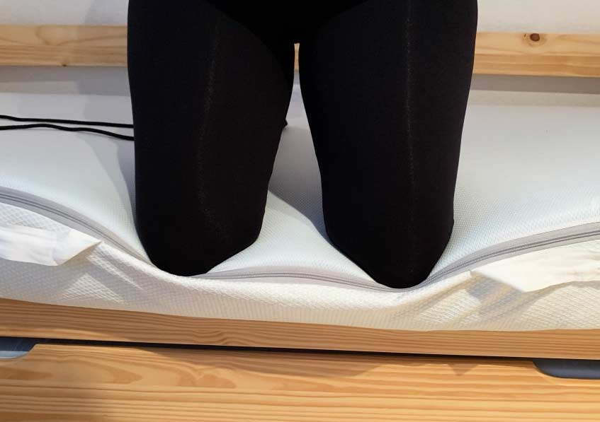 mit beiden Knien auf der Matratze